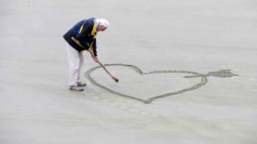 man wearing blue jacket holding a brown stick towards the heart drawn on sand